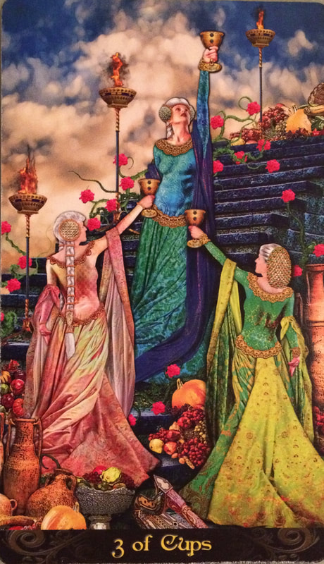 Picture of 3 of cups card showing three women in beautiful gowns lifting cups high in the air